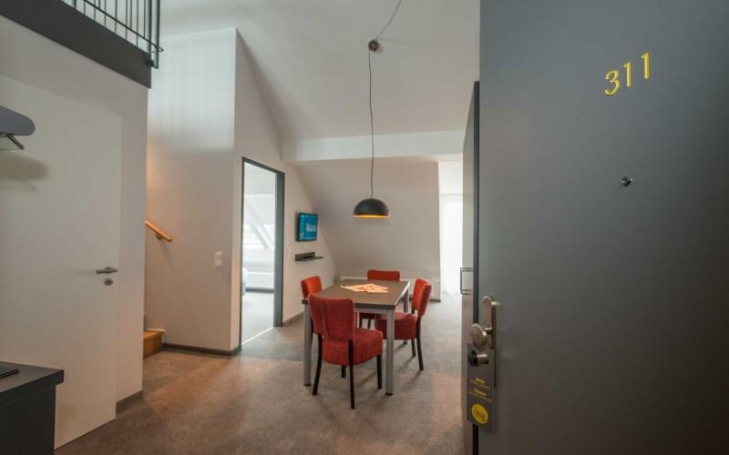 Wohnraum mit Esstisch, Sofa und Küchenzeile
